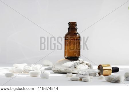 Mock Up Of An Open Glass Dropper Bottle On A Stone Podium On A White Gray Background With Hard Shado
