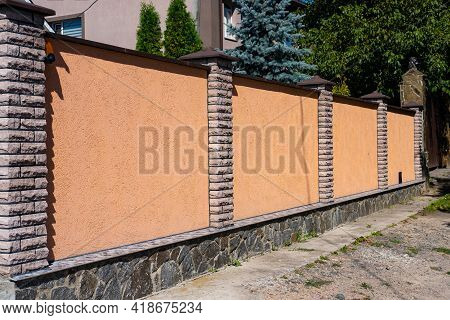 Decorative Concrete Orange Fence With Brick Posts Near A Residential Building With A Garden.