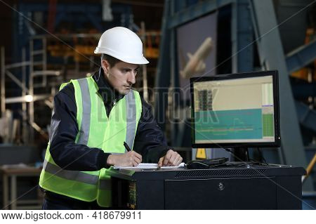 Portrait Of A Man , Factory Engineer In Work Clothes Controlling The Work Process At The Airplane Ma