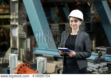 Portrait Of A Female Factory Manager In A White Hard Hat And Business Suit. Controlling The Work Pro