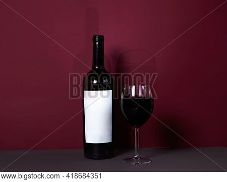 A Glass Of Red Wine Close-up On A Burgundy Background With A Bottle Of Wine In The Background. Styli