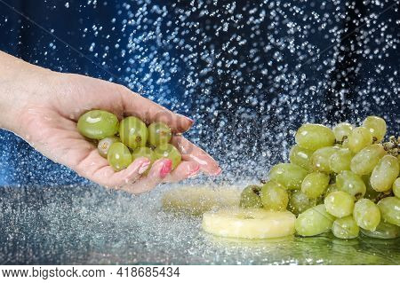 Green Grape Closeup Under The Water Drops. Woman Hand Holding Green Grape. Healthy Lifestyle. Multiv