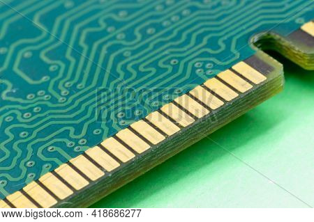 Close-up Gold Contacts Of Computer Memory Module On Green Background. Ram Memory Detail. Concept Ele