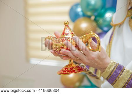 Holding An Old Magic Lamp In His Hand. A Man In Aladdin's Clothes . A Person Holds In His Hand Reali