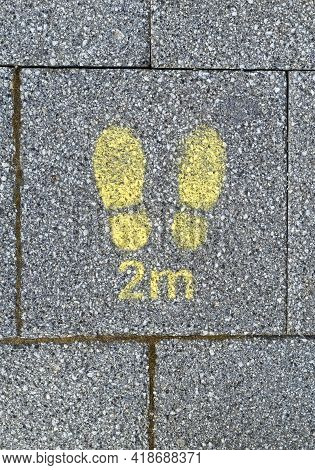 Weston-super-mare, Uk - April 9, 2021: A Sign Stencilled On A Pavement Warning Those Queueing To Kee