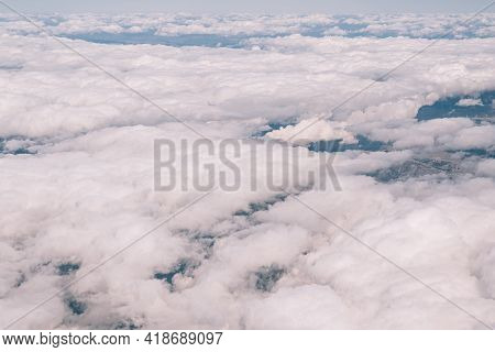 View From The Window Of The Plane On The White Cumulus Clouds In The Sky