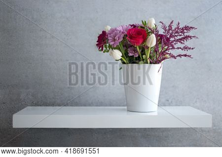 Spring Flowers On Floating White Shelf Against Concrete Wall