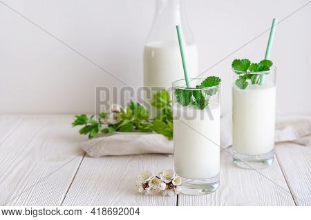 Fresh Fermented Milk Chilled Drink Lassi In Two Glasses On A White Background With Greenery And Flow