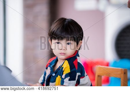 A 2-3 Year Old Asian Boy Shows A Face That He Is Wondering About Something. Cute Baby Wearing A Colo
