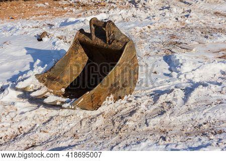 Removable Excavator Bucket Against The Background Of White Snow. Crawler Excavator Bucket