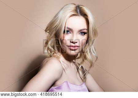 Charming Young Woman With Perfect Makeup On Beige Background. Woman With Beauty Face, Facial Skin Po