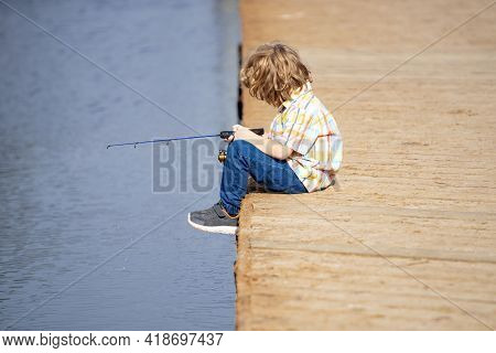 Fishing Concept. Child Fishing On The Lake. Young Fisher. Boy With Spinner At River. Portrait Of Exc