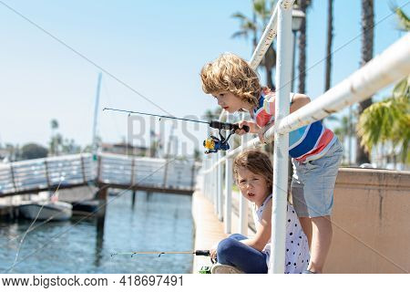 Kids Hobby. Couple Of Kids Fishing On Pier. Child At Jetty With Rod. Boy And Girl With Fish-rod.