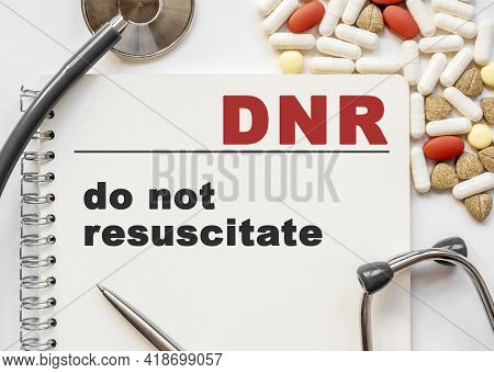 Page In Notebook With Dnr On White Background With Stethoscope And Group Of Pill. Medical Concept. T