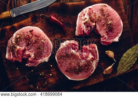 Raw Pork Loin Steaks With Different Spices On Rustic Cutting Board