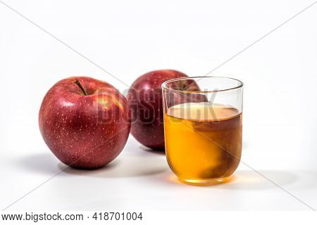 Close Up Of A Glass Of Apple Juice, With A Whole And Half Apple. Natural Apple Juice On White Backgr
