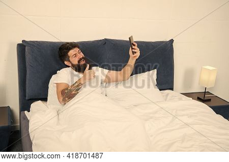 Try Video Calling. Happy Hipster Thumbs Up To Video Camera. Bearded Man Make Video Call In Bed. Vide