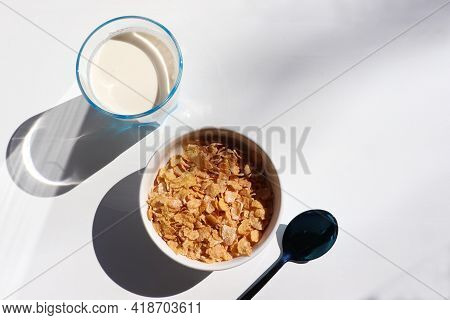 Bowl Of Cereal And Glass Of Milk On White Background. Healthy Breakfast With Cornflakes And Milk. To