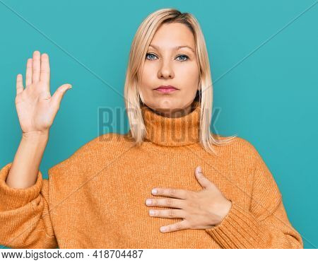 Middle age caucasian woman wearing casual winter sweater swearing with hand on chest and open palm, making a loyalty promise oath