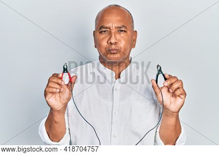 Middle age latin man holding battery charge clippers puffing cheeks with funny face. mouth inflated with air, catching air.