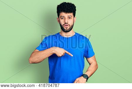 Young arab man with beard wearing casual blue t shirt in hurry pointing to watch time, impatience, upset and angry for deadline delay