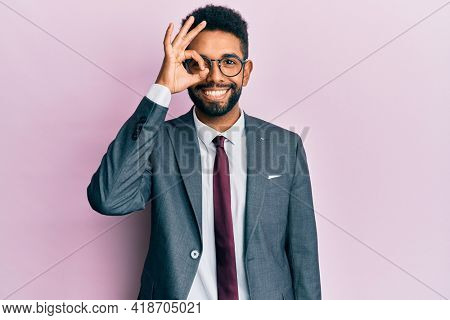 Handsome hispanic business man with beard wearing business suit and tie doing ok gesture with hand smiling, eye looking through fingers with happy face.