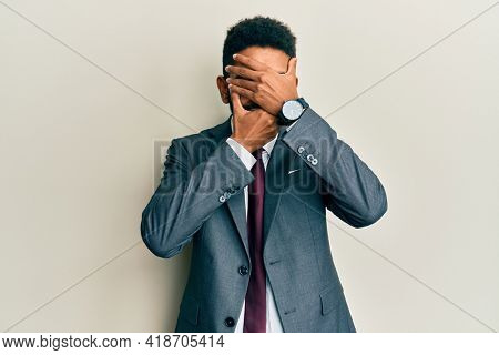Handsome hispanic man with beard wearing business suit and tie covering eyes and mouth with hands, surprised and shocked. hiding emotion