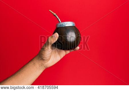 Hand of hispanic man holding cup of mate infusion beverage over isolated red background.