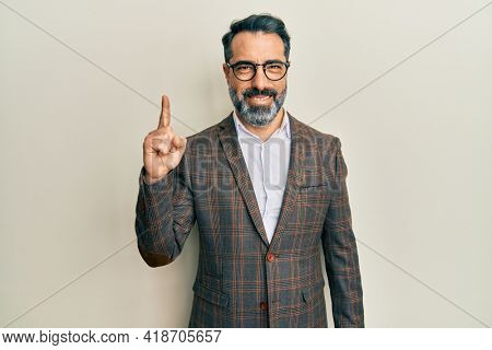 Middle age man with beard and grey hair wearing business jacket and glasses showing and pointing up with finger number one while smiling confident and happy.