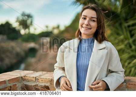 Young hispanic woman smiling happy leaning on the wall at the park.