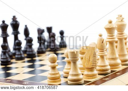 Wooden Chess. Chess Pieces Arranged On A Chessboard. Isolated On White Background. Closeup