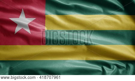 Togolese Flag Waving In The Wind. Close Up Of Togo Banner Blowing Soft Silk.