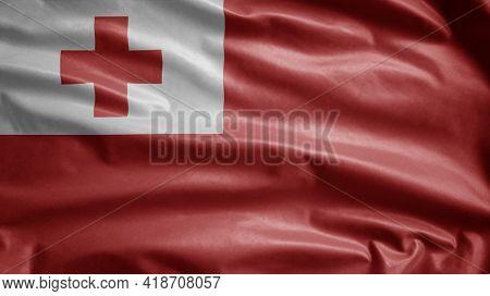 Tongan Flag Waving In The Wind. Close Up Of Tonga Banner Blowing Soft Silk.