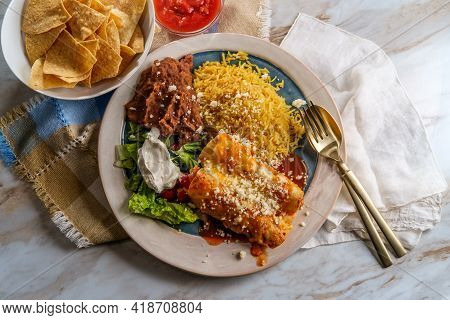 Traditional Mexican Enchiladas Dinner Served With Rice And Refried Pinto Beans