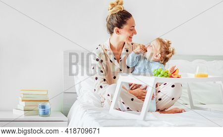 Mother And Daughter Having Breakfast In Bed With Fruits In Pyjamas - Family Concept