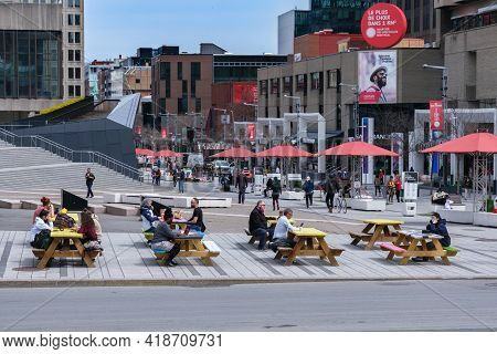Montreal, Ca - 28 April 2021: People Sitting At Picnic Tables On Ste Catherine Street In Montreal Do