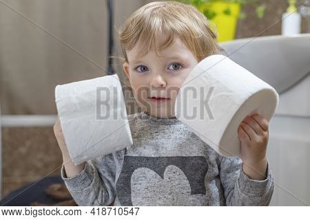 A Cute Boy Is Holding Toilet Paper Roll In Bathroom. Young Boy With Toilet Paper.