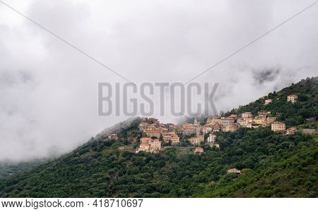 Mountain Village Of Belgodere Surrounded By Woodland In The Balagne Region Of Corsica Under A Blanke