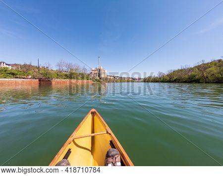 Caucasian Man Paddling In A Pack Canoe Down The Monongahela River In Morgantown, West Virginia
