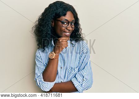 Beautiful african young woman wearing casual clothes and glasses smiling looking confident at the camera with crossed arms and hand on chin. thinking positive.