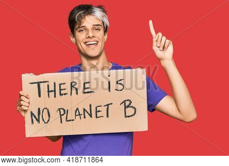 Young hispanic man holding there is no planet b banner surprised with an idea or question pointing finger with happy face, number one