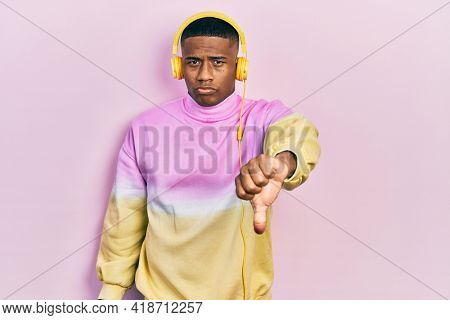 Young black man listening to music wearing headphones looking unhappy and angry showing rejection and negative with thumbs down gesture. bad expression.