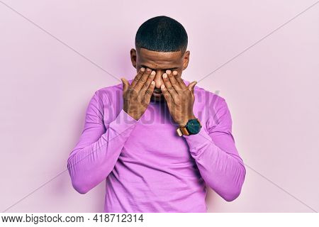 Young black man wearing casual pink sweater rubbing eyes for fatigue and headache, sleepy and tired expression. vision problem