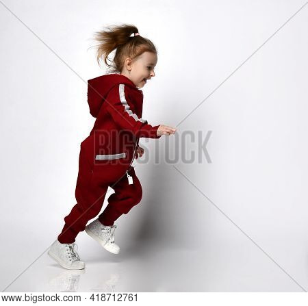 Cute Smiling Little Preschool Girl Dressed In A Warm Hooded Tracksuit And White Sneakers Runs Across
