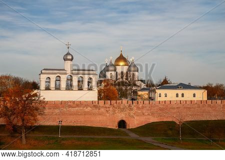 Novgorod Kremlin, Russia. Belfry And St. Sophia Cathedral Over A Red Brick Wall