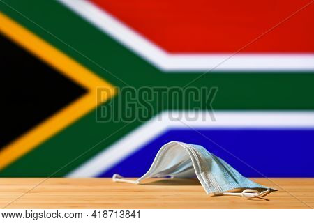 A Medical Mask Lies On The Table Against The Background Of The Flag Of South Africa. The Concept Of