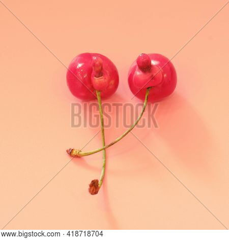 Unusual Mutated Cherry On A Orange Background, The Concept Of Gmo Products, Two Fused Berries