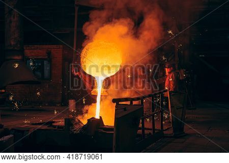 Metallurgical Plant, Hot Liquid Metal Pouring Into Special Mold In Foundry With Worker.