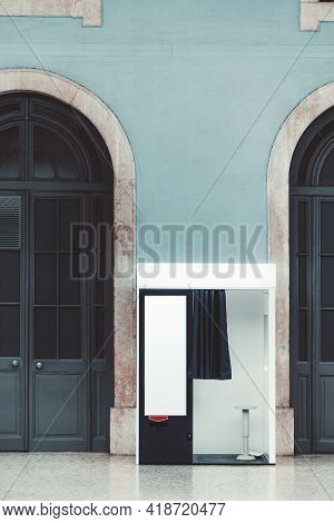 Vertical Shot Of An Indoor Empty Photo Booth With Open Curtain, In Between Two Wooden Arch Doors For