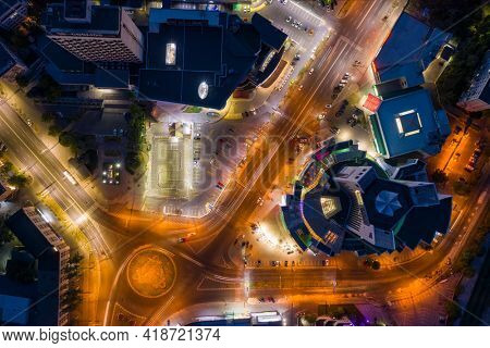 Chisinau, Moldova, August 2020: Aerial drone view of night illuminated downtown traffic cirle near the Atrium building, long exposure